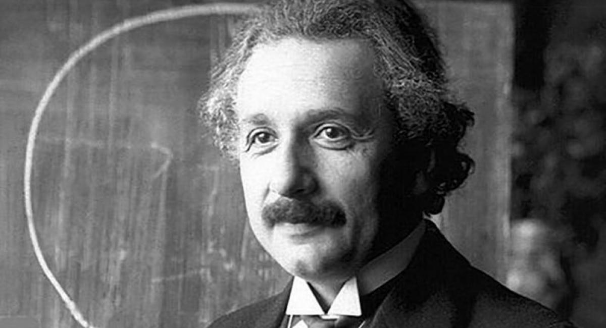 Albert Einstein in front of a blackboard.